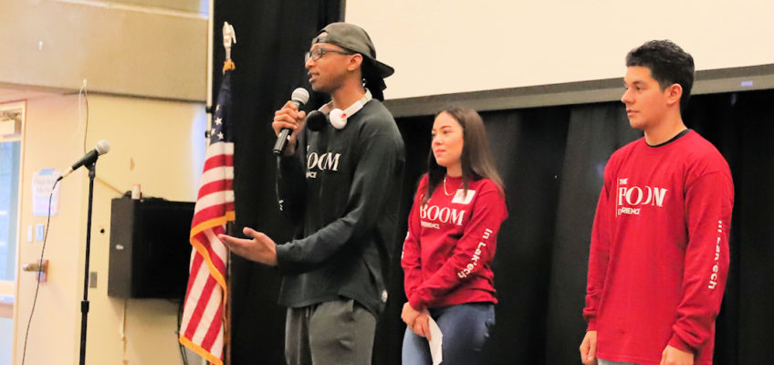 Three students, on stage at the 2018 The BOOM Experience event