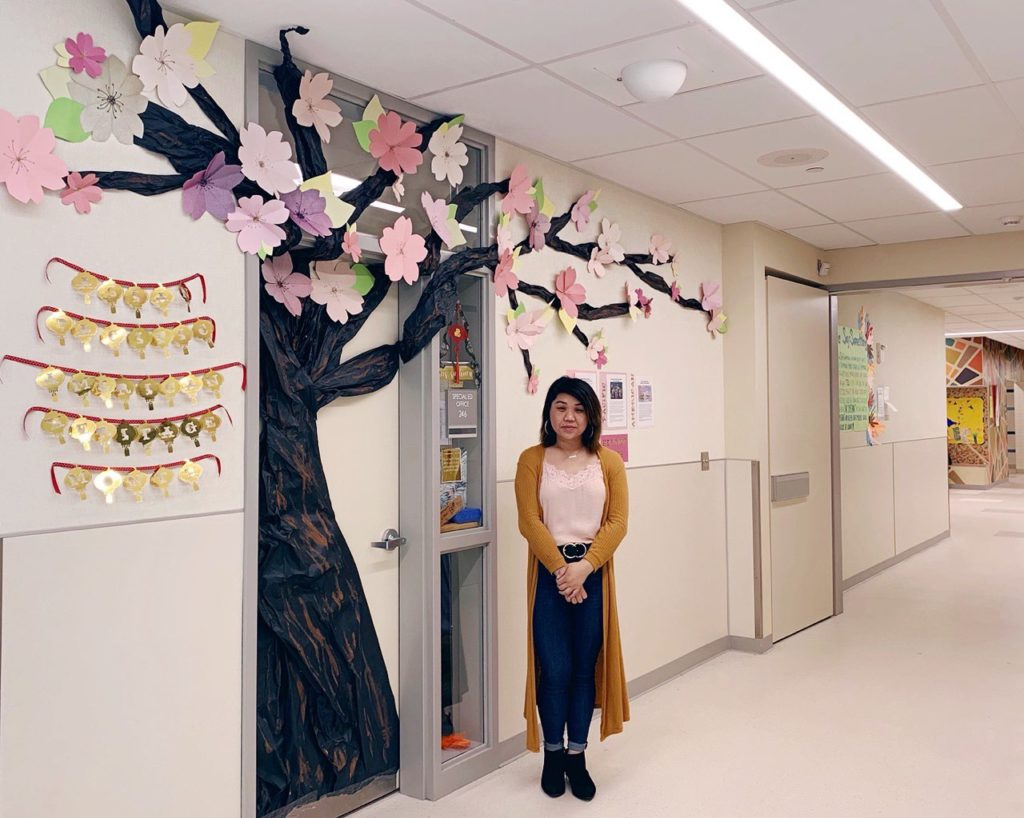 a woman standing in front of a door she decorated like a cherry blossom tree for Asian Pacific American Heritage Month
