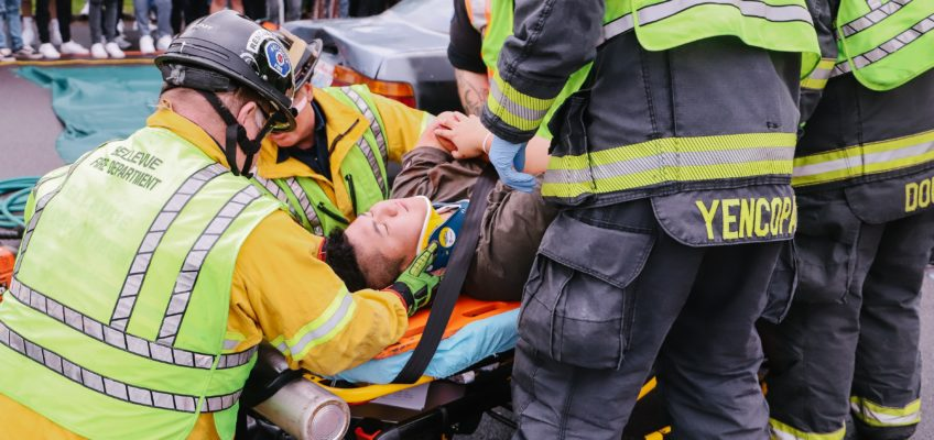 a person on a stretcher, holding their arm as firefighters help them