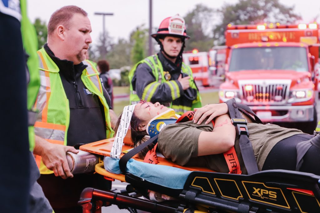 a girl on a stretcher with firefighters helping her