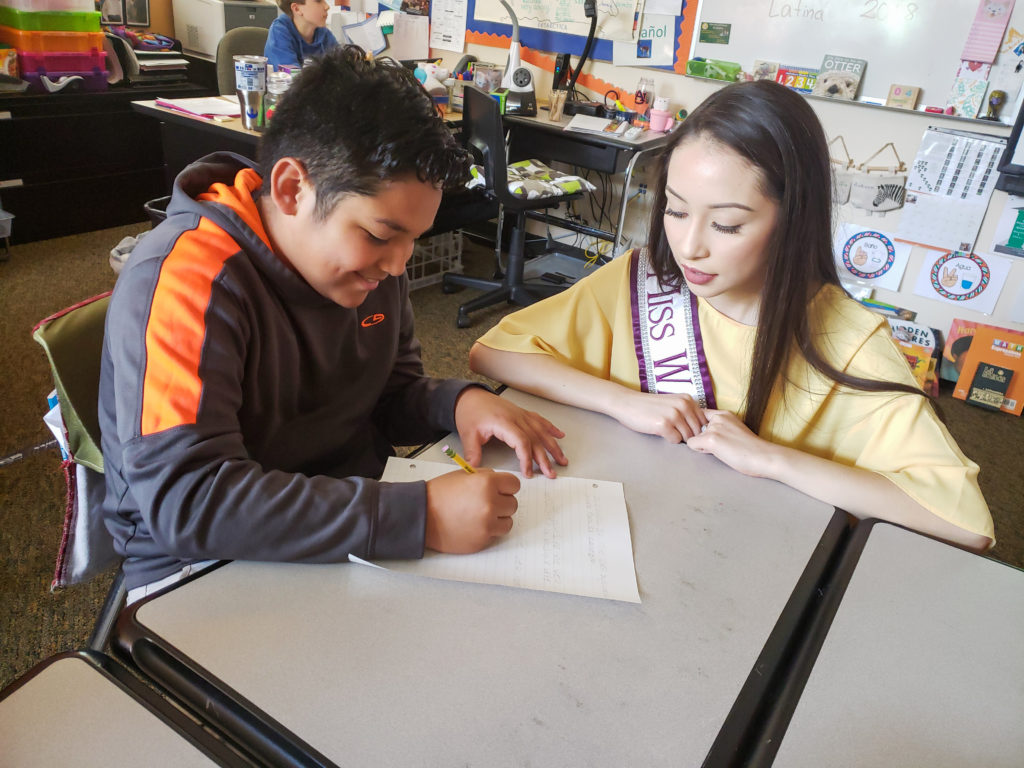 Miss Washington Latina helping a student write out their goals