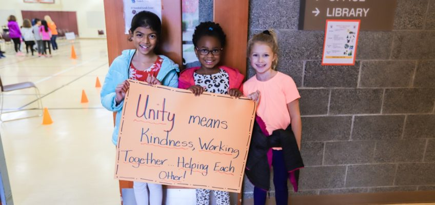 "students holding up a poster that says ""Unity means Kindness, Working Together...Helping Each Other!"""