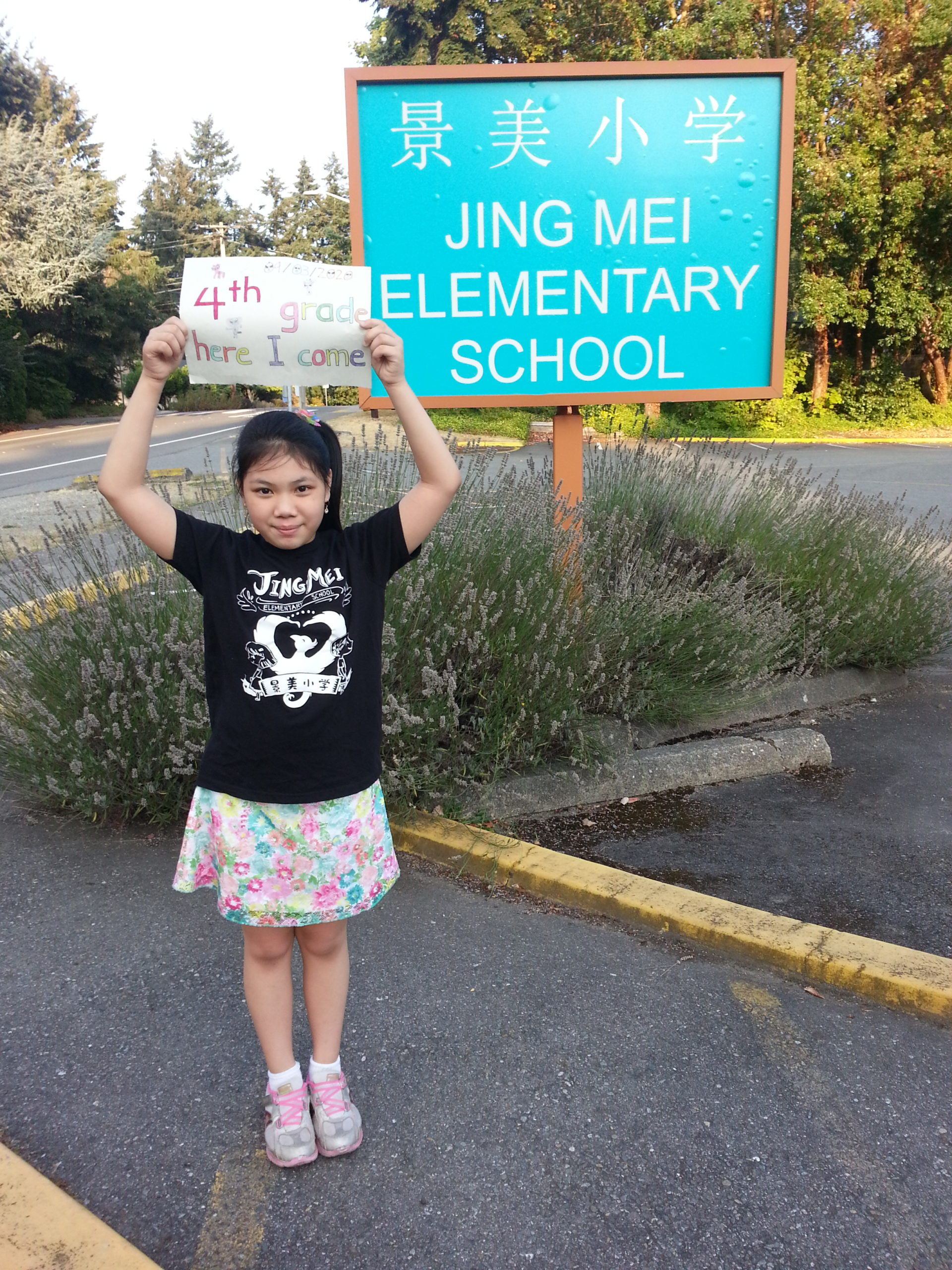 a student standing outside of Jing Mei Elementary holding a BSD first day sign