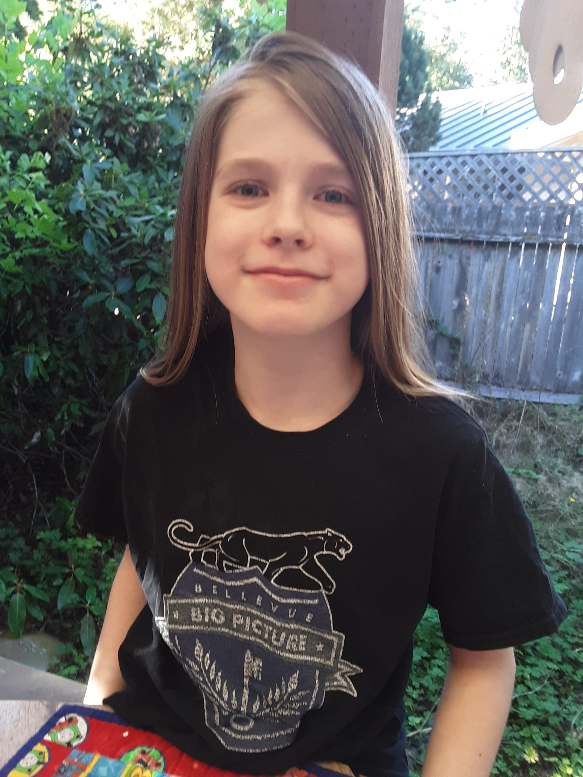 a student smiling and wearing a big picture shirt