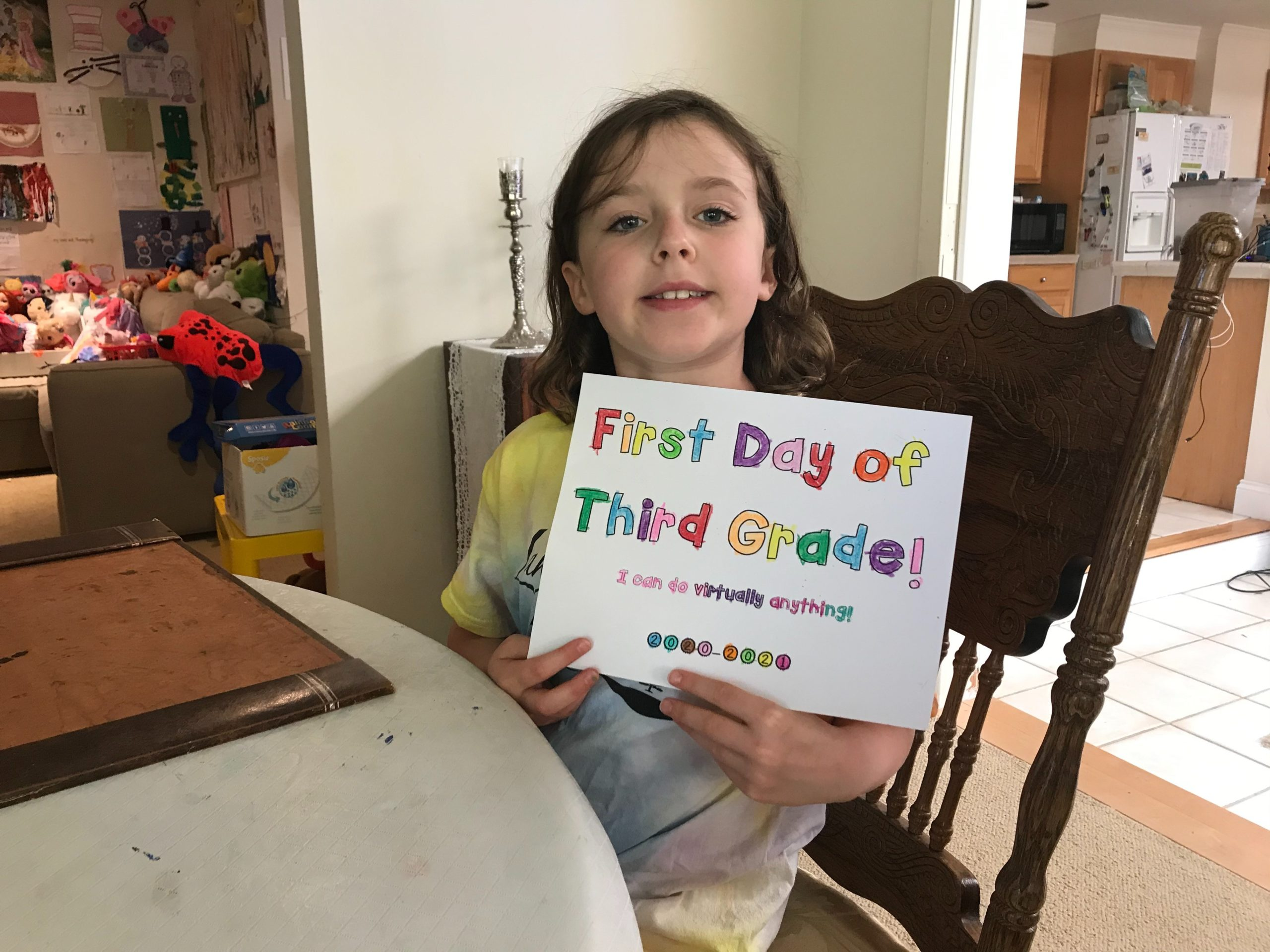 a student smiling and holding a sign that says first day of third grade