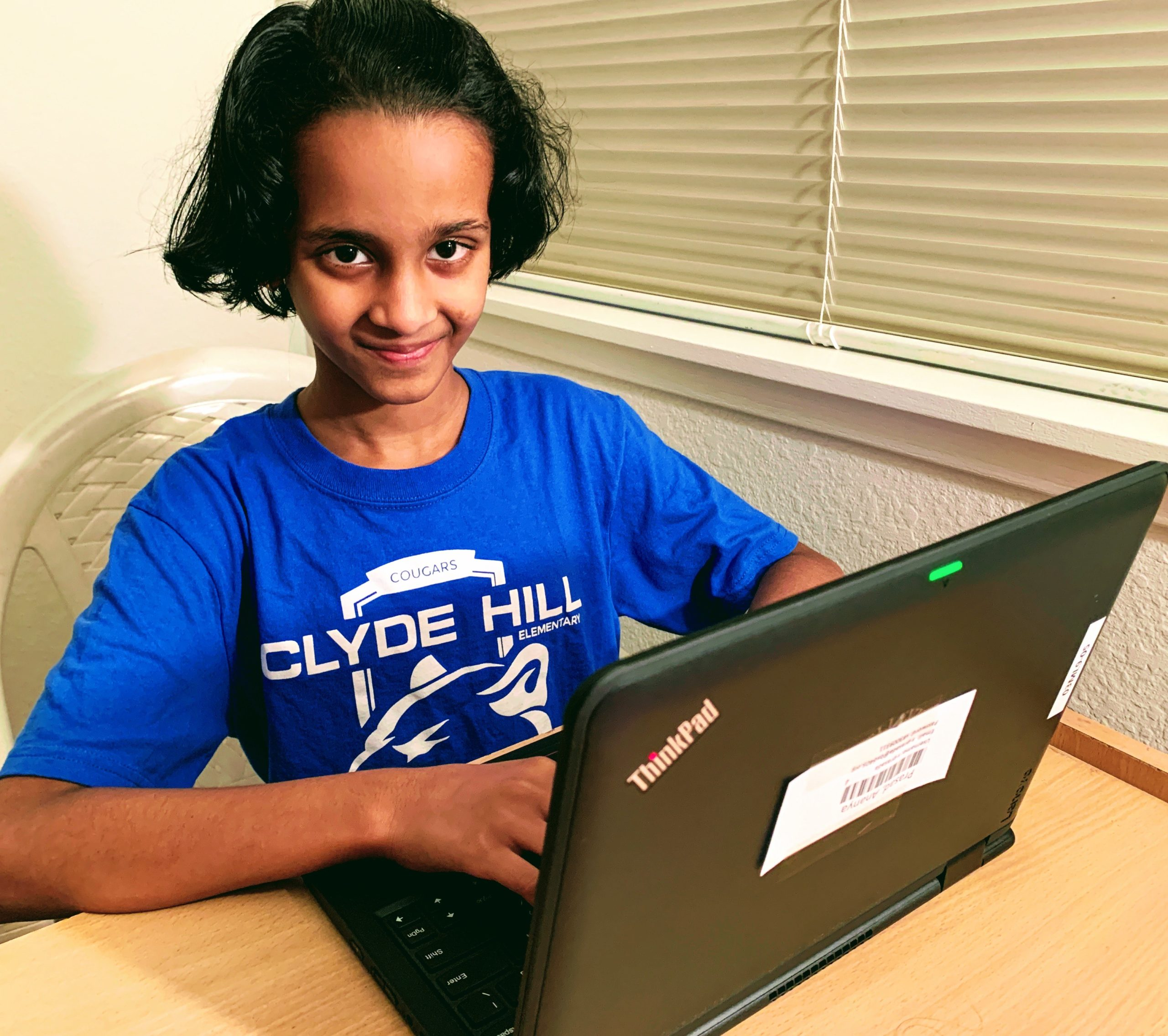a student wearing a Clyde Hill shirt while typing on a laptop