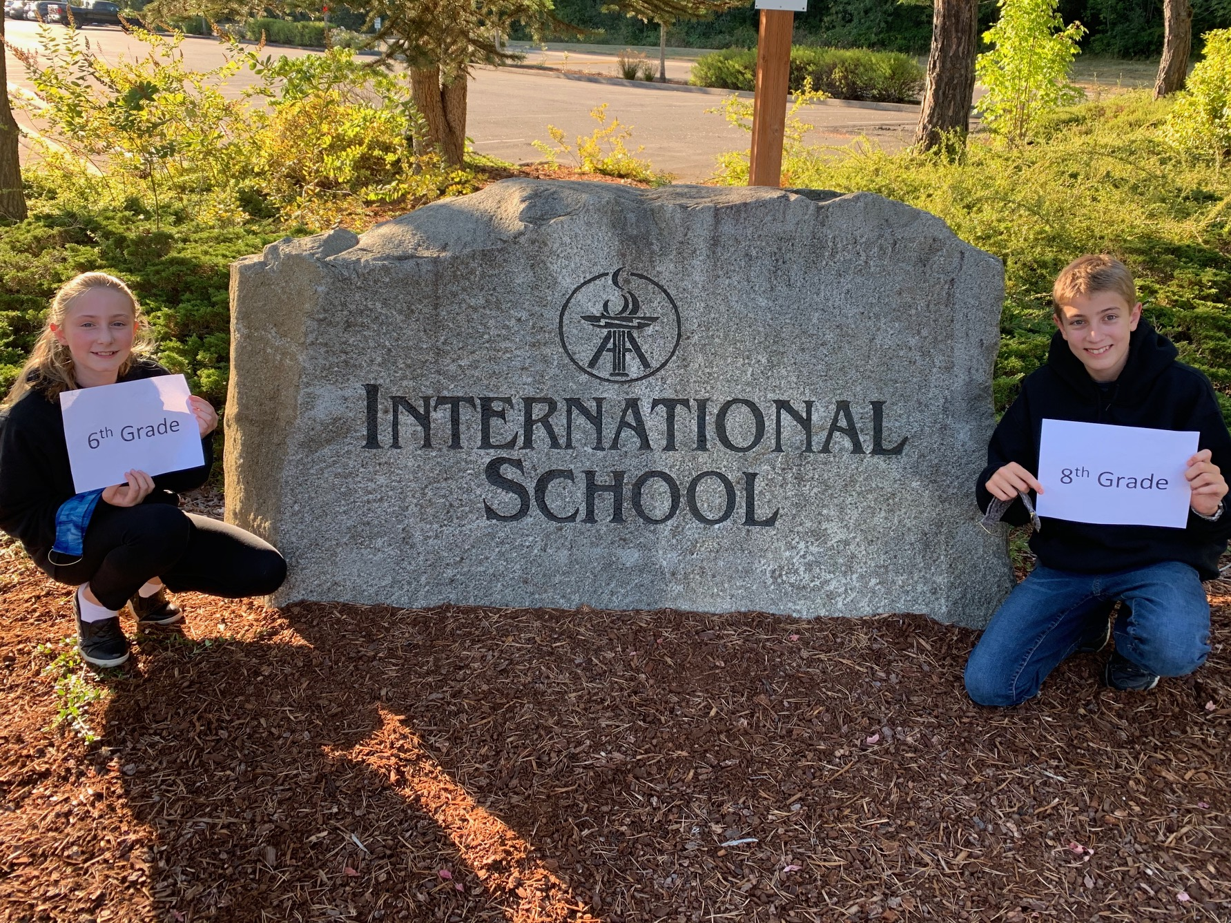 Students smiling in front of the International School sign