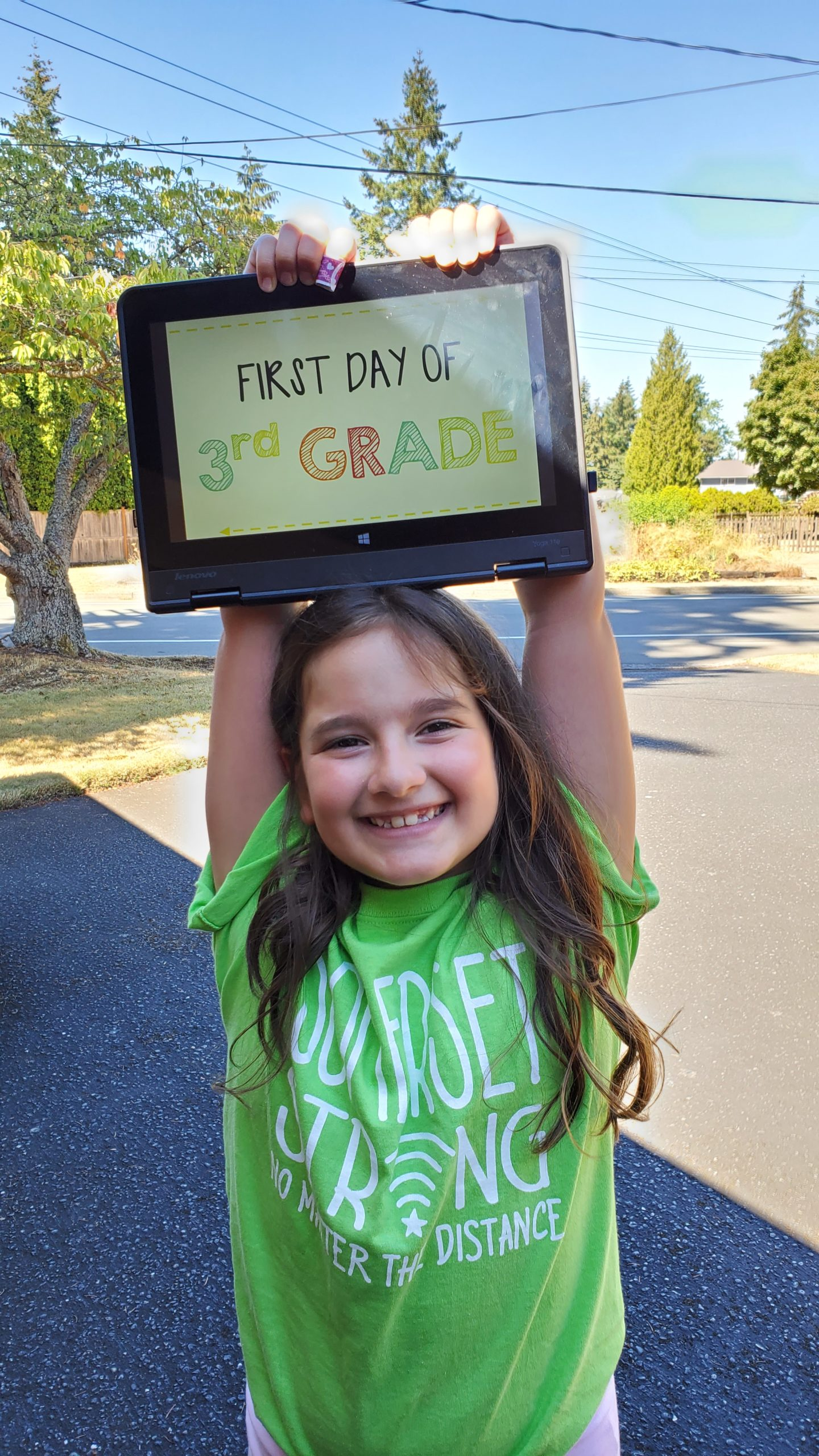 a student smiling, wearing a Somerset shirt and holding a BSD first day sign