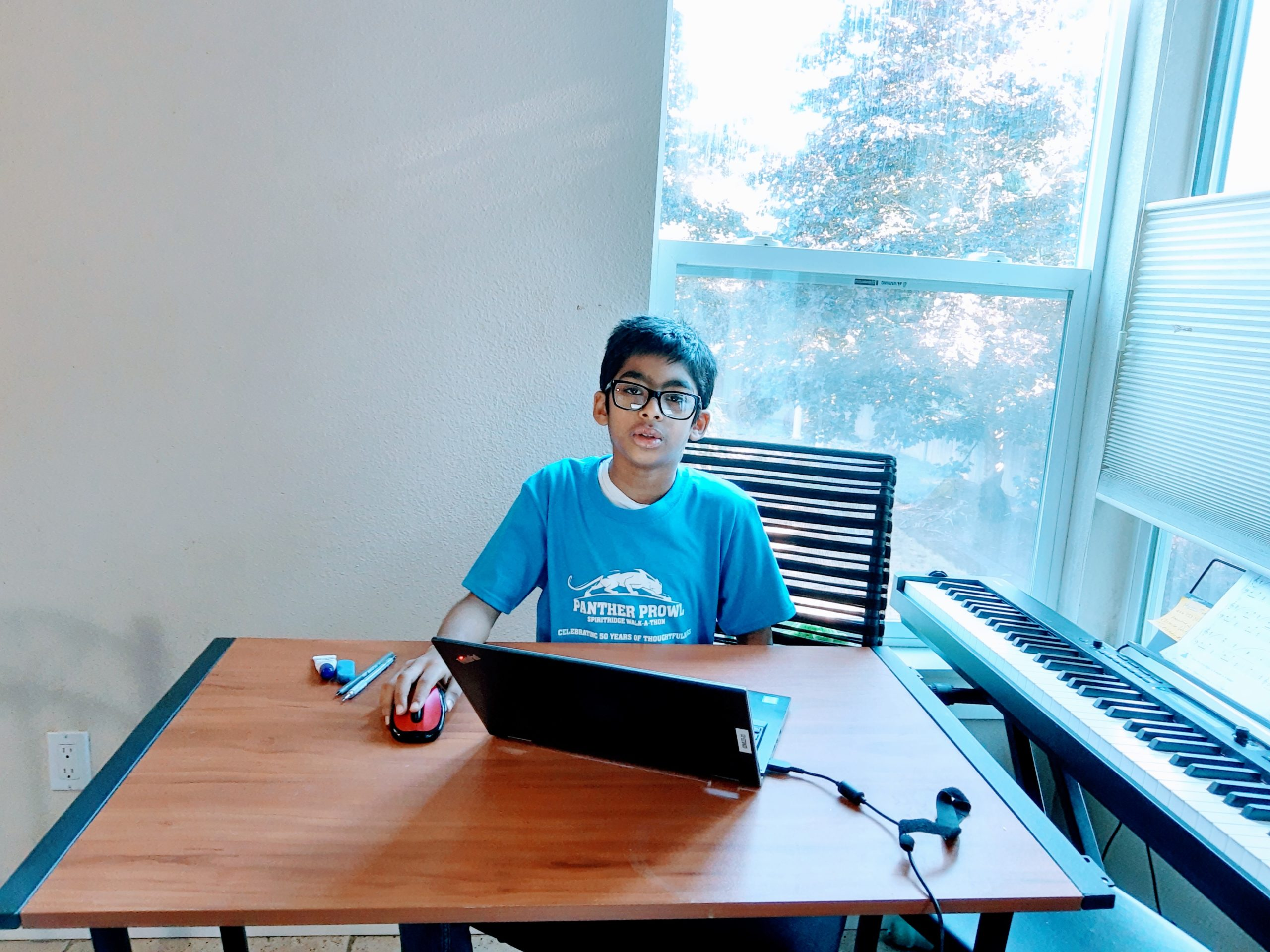 a student sitting at a desk using a laptop