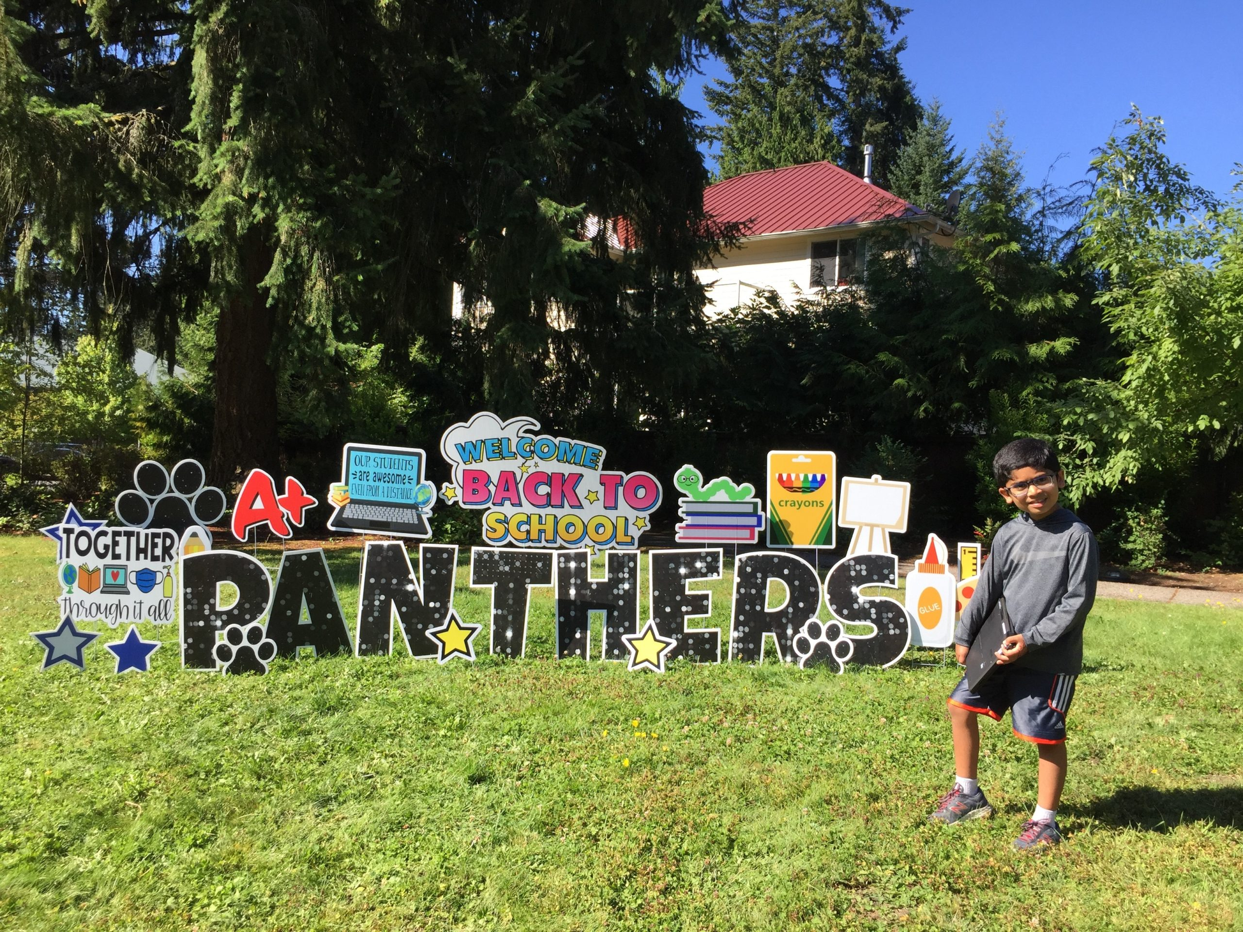 A student smiling in front of a Panthers sign