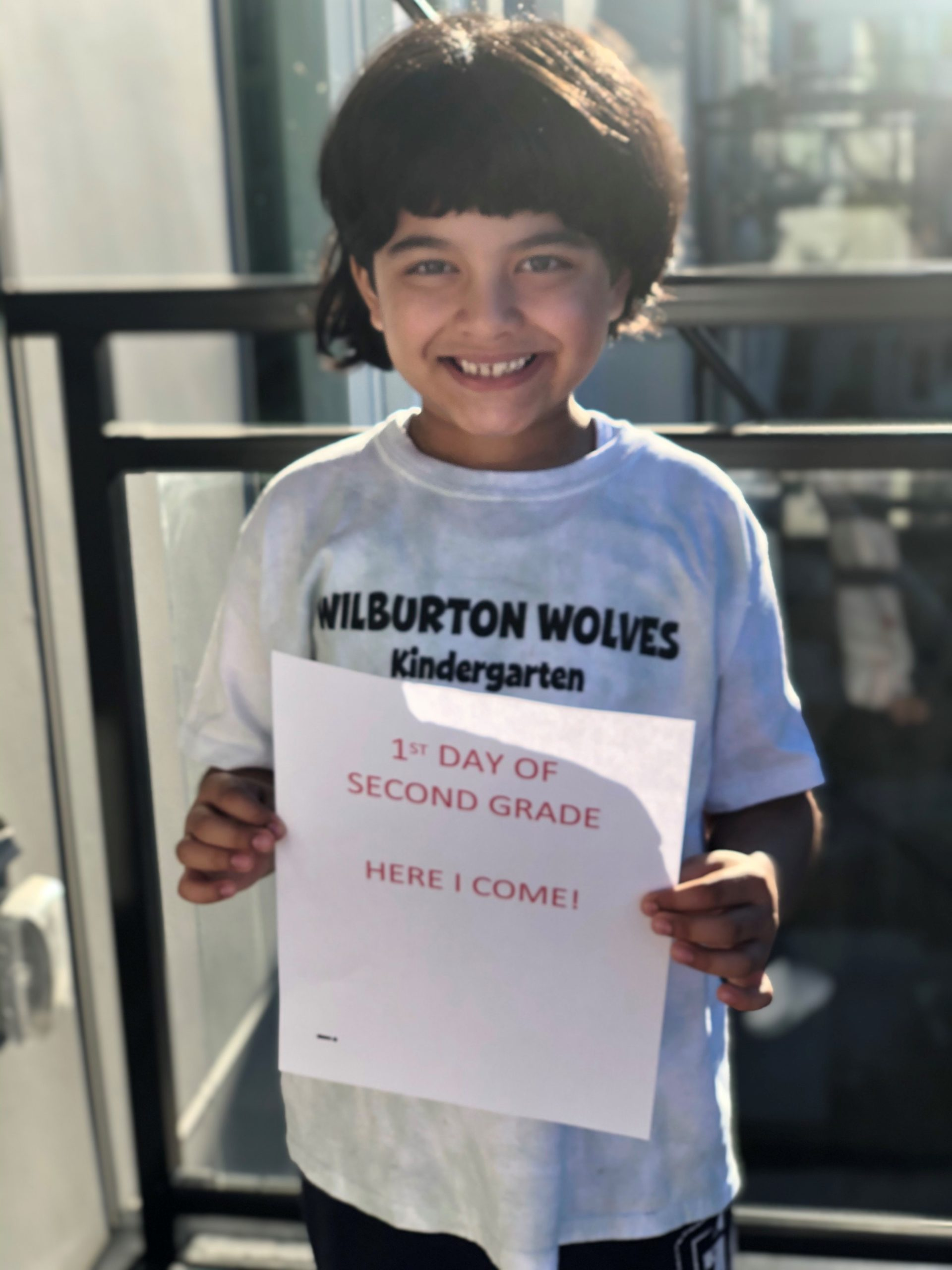 A student smiling, wearing a Wilburton shirt and holding a BSD first day sign