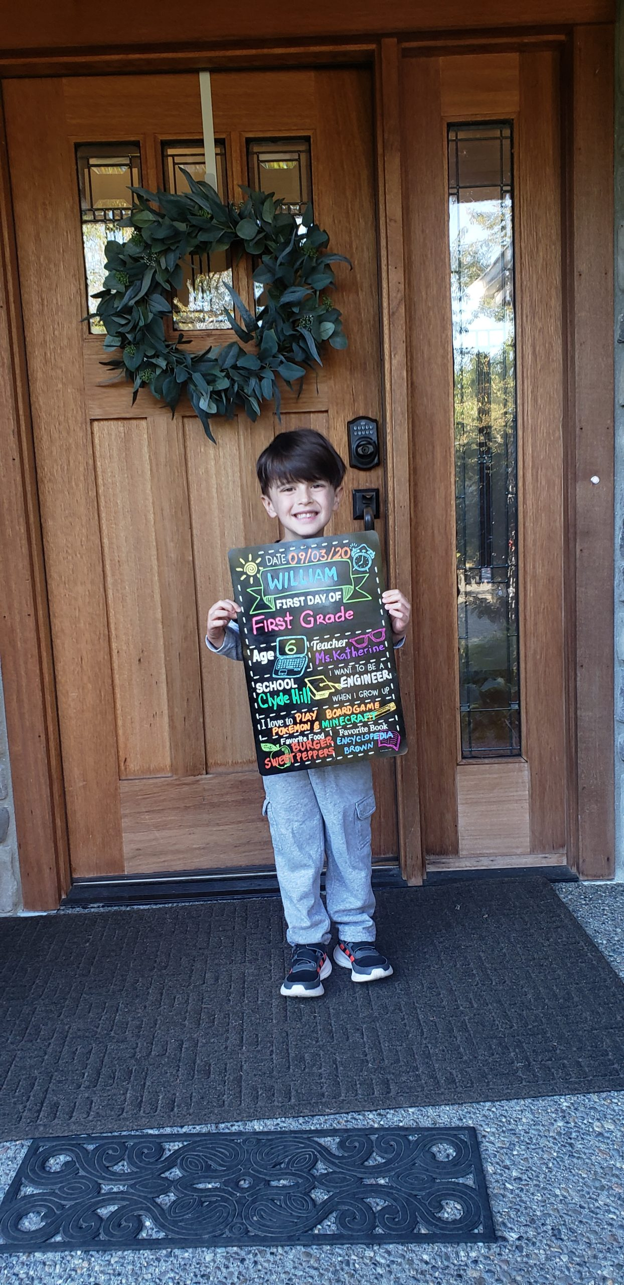 a student holding a BSD first day of school sign