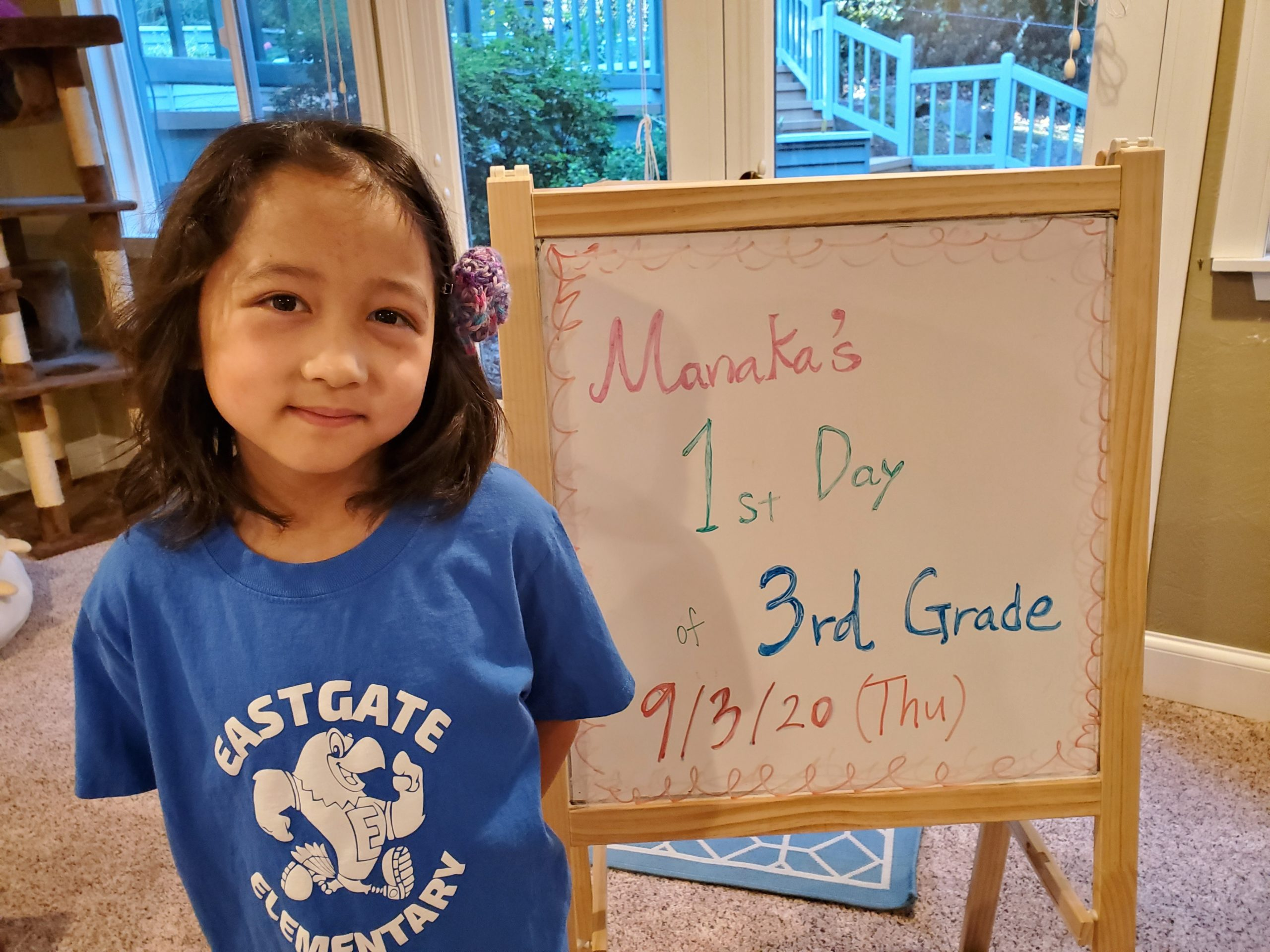 a student in front of a sign that says Manaka's 1st day of 3rd grade