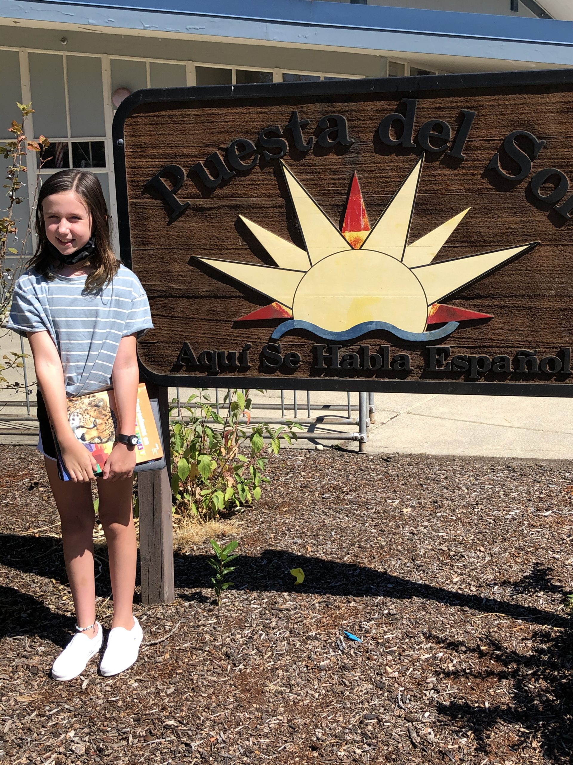 a student smiling in front of the Puesta del Sol sign