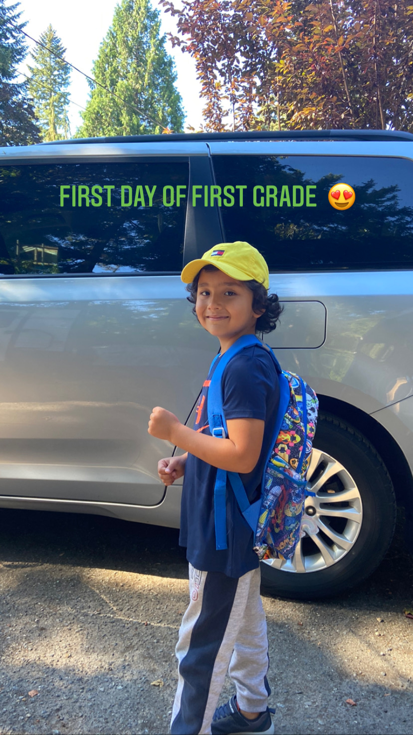 a student smiling with text on the photo that says first day of first grade