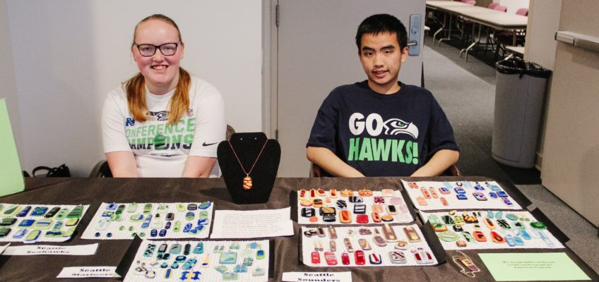 Melissa and Albert smile for a photo while they sell glass art