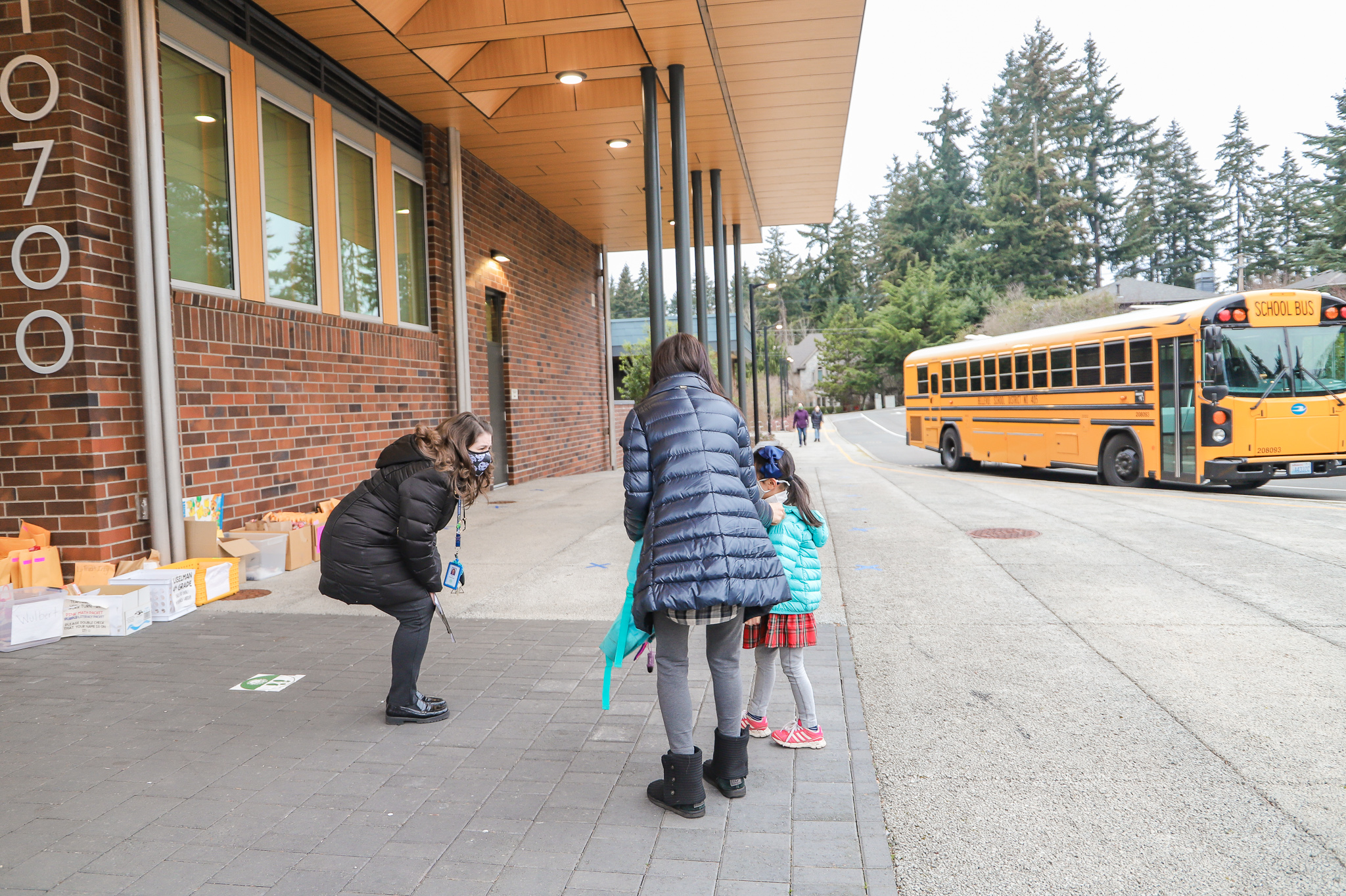 a staff member talking to a kindergartener and their parent