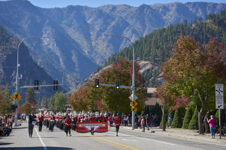 Newport Pride Marching Band performing in a parade in front of a mountain